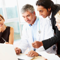 business team looking at something on laptop with doctor